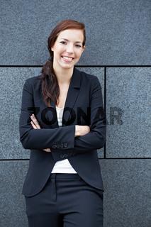 Geschäftsfrau lehnt an Mauer