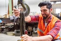 Arbeiter in einer Fabrik befestigt Last an einem Kranhaken