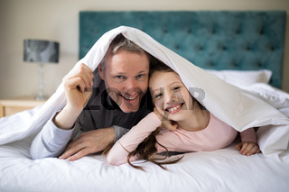 Smiling father and daughter lying on bed in bedroom