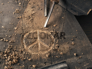 The peace symbol carved in wood with chisels. Peace concept, global solidarity