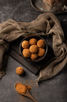 Homemade delicious cocoa balls with healthy ingredients in a black plate, covered with cocoa powder