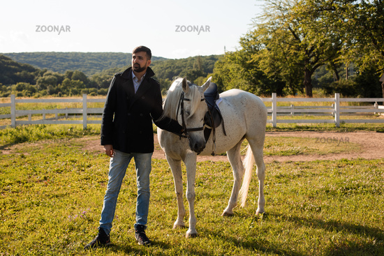 Man with a horse on a background of beautiful nature