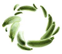 Green zucchini levitate on a white background