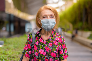 Outdoors portrait of senior tourist woman wearing disposable medical face mask and thinking. Safety in public place during coronavirus outbreak.