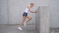 Female athlete exercising near barrier