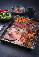 Traditional Commonwealth Sunday roast with sliced cold cuts roast beef with fried onion rings and chili served as close-up on an old rustic metal tray