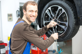 Kfz Mechatroniker beim Reifenwechseln an Hebebühne