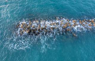 Aerial view from a flying drone of blue sea water and break water. Sea wall coastline