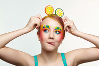 Teenager girl with unusual face art make-up show tongue. Child with lollipops in hands on head like ears.