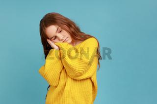 Portrait of tired sleepy little girl sleeping with hands near head, needs energy, keeps eyes closed.