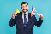 Satisfied man with beard wearing official style suit holding USA flag and paper house, dreaming to buy accommodation in America, looking at camera.