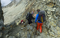 Alpinisten an einer engen Felspassage am Tracuit-Pass, Val d'Anniviers, Wallis, Schweiz
