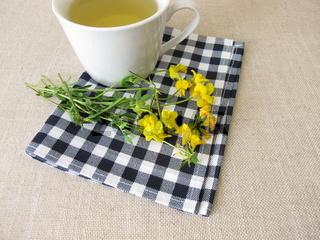 Eine Tasse Tee mit den gelben Blüten vom Hornklee