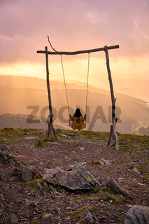 Woman girl social distancing swinging on a Swing baloico in Lousa mountain, Portugal at sunset