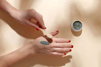 hands applying blue cosmetic clay mask to skin