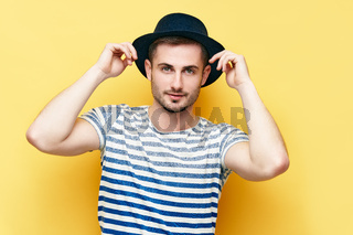 Young hipster man in hat over yellow background