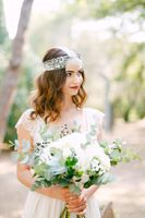 The bride is holding a wedding bouquet of roses, eucalyptus branches, delicate white flowers and dark berries in her hands