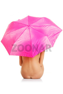 Beautiful nude woman under pink umbrella
