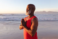 Senior african american man with folded hands meditating and practicing yoga at the beach