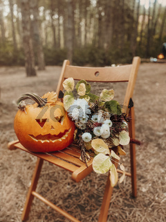 Carved orange pumpkin jack-o-lantern with spooky face on wooden chair in forest