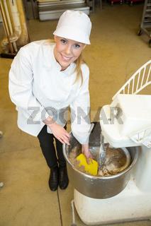 Bäckerin bedient Teig Knetmaschine in Bäckerei