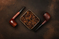 Tin of coarse cut tobacco and pipes over brown