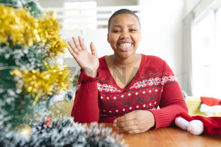 Happy african american plus size woman i making christmas video call on laptop
