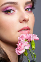 Closeup portrait of female face with pink beauty makeup and carnation flowers near lips.