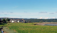 view of the village of arnside from the bank of the river kent with surrounding lakeland scenery