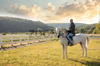 The young man is riding a horse on a farm