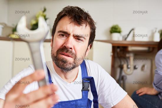 Heimwerker mit Maulschlüssel blickt unsicher