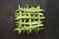 Top view of whole green beans in a geometric pattern on dark background