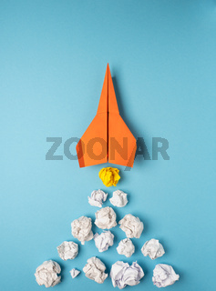 Launching paper rocket with jet stream of paper balls, creativity concept or new ideas metaphor, start up business