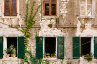 An old residential building in cracks with windows and shutters and flowers on the windowsills.