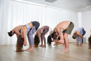Group of young sporty attractive people in yoga studio, practicing yoga lesson with instructor, standing, stretching and relaxing after workout . Healthy active lifestyle, working out indoors in gym