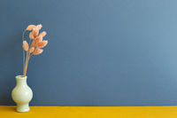 Vase of pink dry flowers on yellow wooden table. blue wall background. home interior