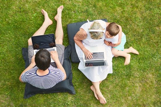 Neugieriges Kind und Eltern am Laptop auf dem Rasen