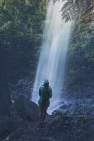 Woman hiker standing below a waterfall after rain