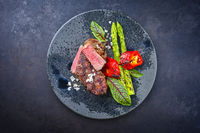 Modern style barbecue dry aged wagyu roast beef steak with green asparagus and lettuce offered as top view on a Nordic design plate with copy space
