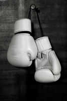 White leather boxing gloves hanging on black wall
