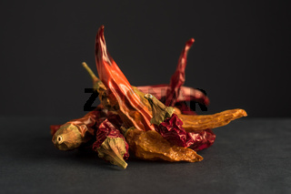 Dried red and yellow chillies on dark background