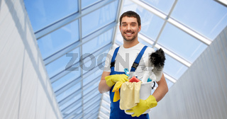 male cleaner with cleaning supplies in glasshouse