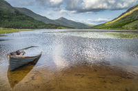 Sunken paddle boat in Lough Gummeenduff with view on beautiful Black Valley