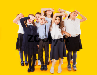 Schoochildren with backpacks and crossed hands standing over yellow background