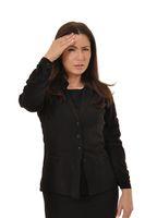 Frau mit Kopfschmerzen haelt eine Hand an den Kopf