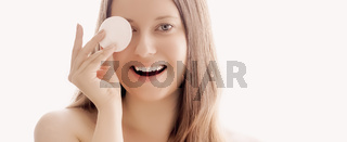 Beautiful woman with cotton pad, perfect skin and shiny hair as make-up, health and wellness concept. Face portrait of young female model for skincare cosmetics and luxury beauty ad design