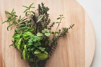 Bundle of Mediterranean herbs for cooking on a round wooden cutting board