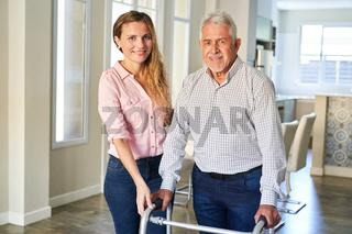 Senior nach Schlaganfall mit Rollator betreut von seiner Tochter