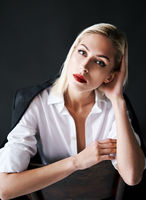 Close up portrait of beautiful blonde woman with red lips in elegant white shirt posing isolated on black studio background