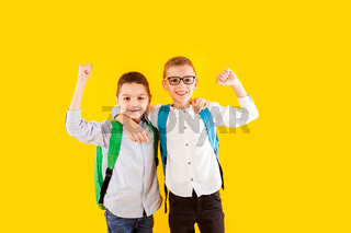 Two school friends stand in an embrace and smile
